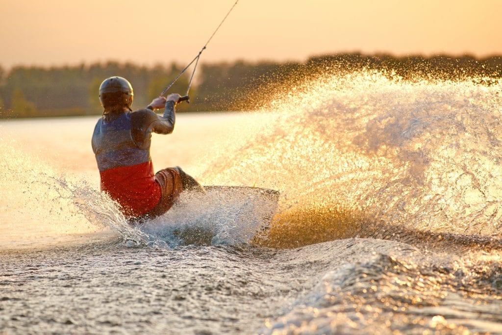 man wakeboarding at sunset