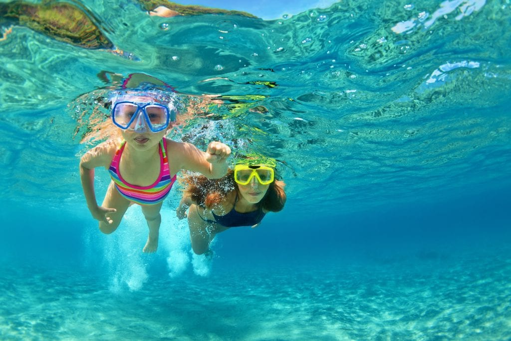 children swimming on a family holiday