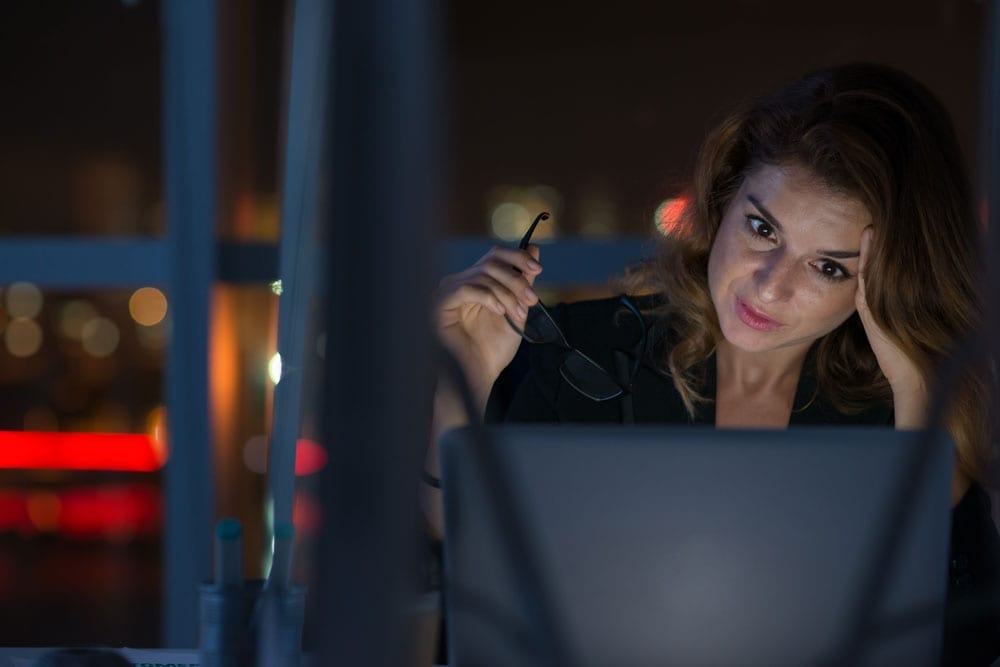 lady staring at laptop at night