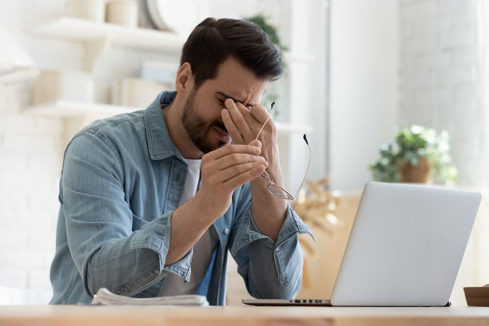 young professional stressed at laptop
