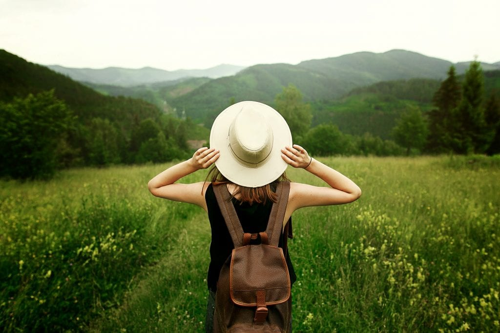 lady holding her hat while looking out to the open green field