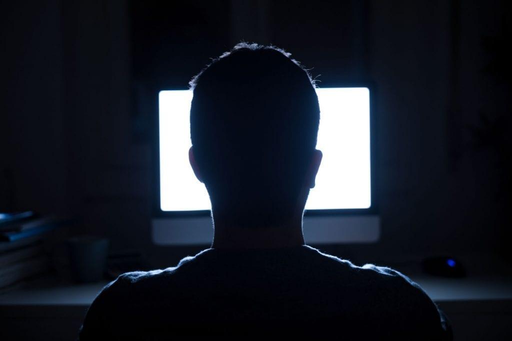 man using computer at night