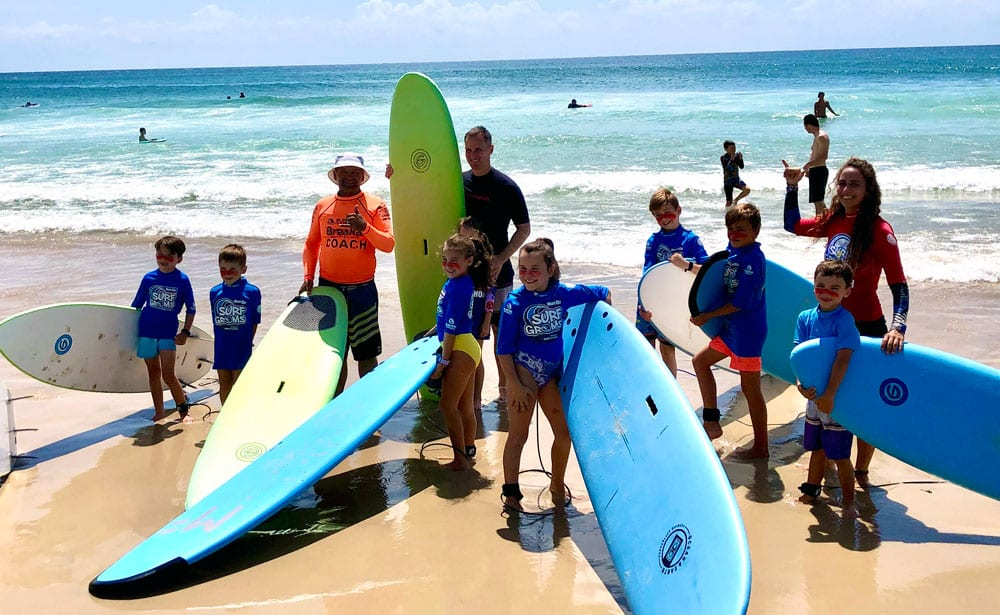 Surf instructors and children posing for photo at beach.