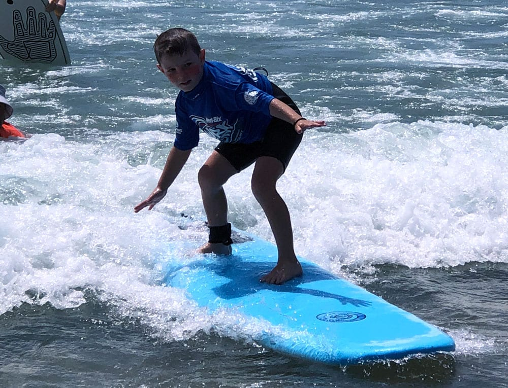 young boy surfing at godfather surf school