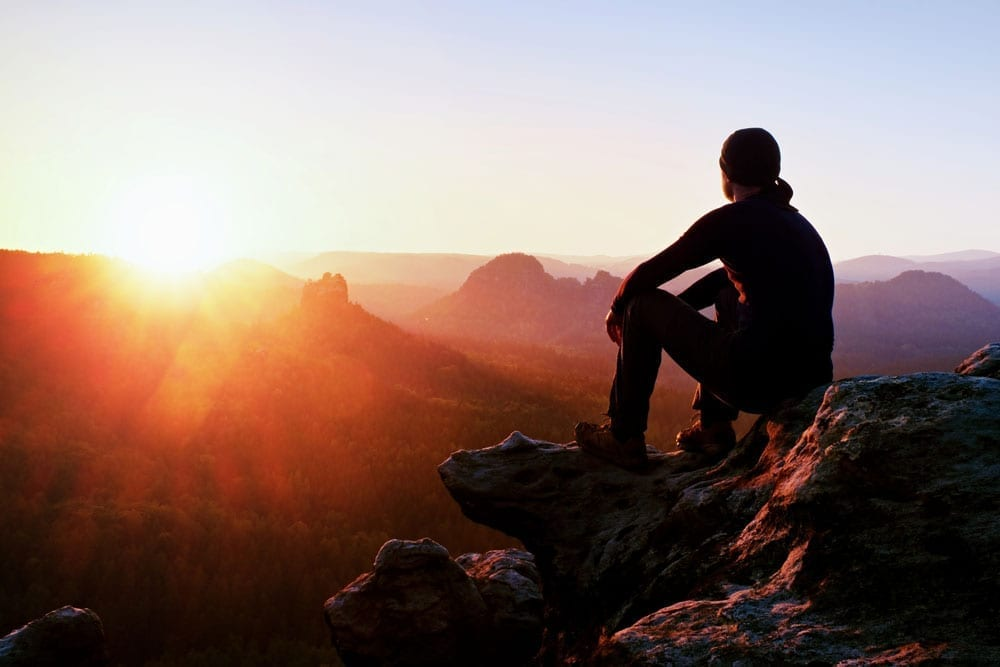 man gazing at mountain sunset