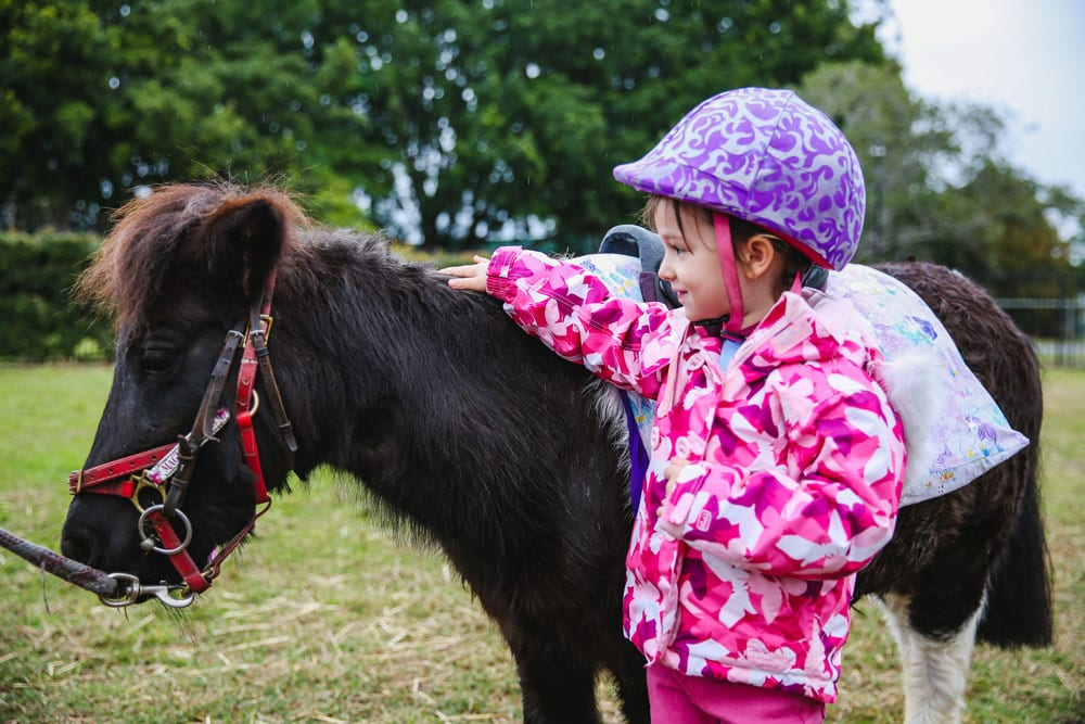 Young girl patting a pony at Markets in the Meadow