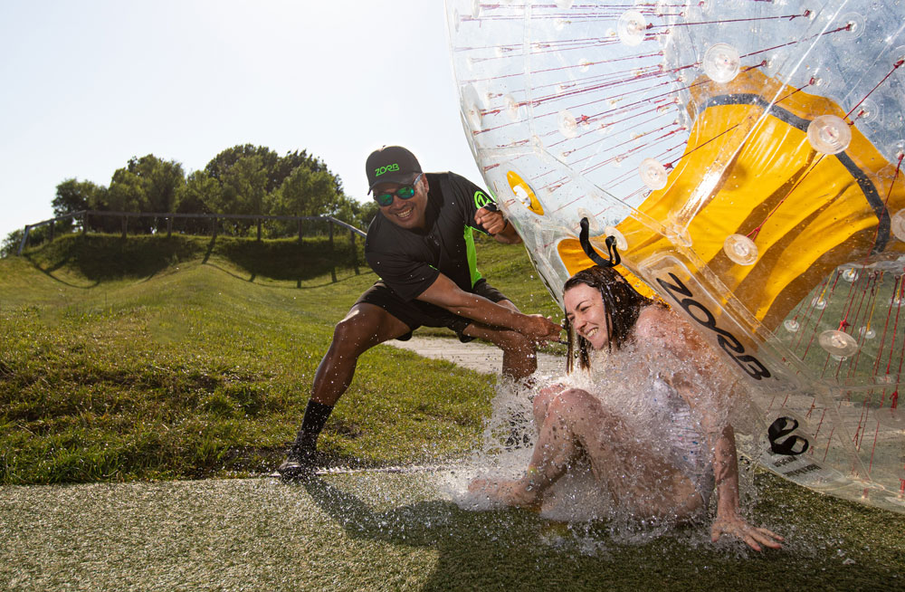 woman and zorb team member exiting a zorb